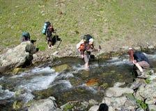 穿过河的小组登山人 库存照片