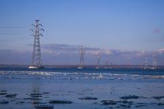 穿过河的电送电线反对 库存照片