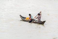 穿过河的缅甸夫人通过用浆划一条小船 库存照片
