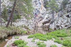 穿过河的登山家 免版税库存图片