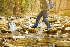 穿过石头的远足者人一条河,腿看法  免版税图库摄影