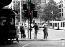 穿过碎片街道的三个人等待在墨尔本,澳大利亚 库存照片