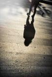穿过街道的一个人的阴影 图库摄影