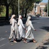 穿过街道的三位宽容黑人尼姑在罗马 库存照片