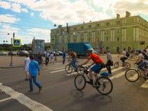 穿过街道的人们和骑自行车者 都市日常生活在圣彼德堡 库图佐夫堤防 俄国 夏天2017年 免版税库存图片