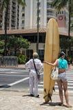 穿过街道的冲浪者女孩在威基基 免版税图库摄影