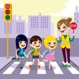 穿过街道的学校学生 免版税库存照片