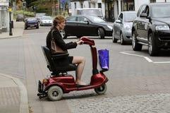 穿过街道的流动性滑行车的妇女 免版税图库摄影