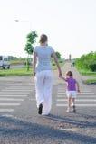 穿过路的母亲和孩子。 库存图片