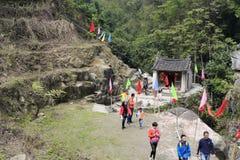 穿过遥远的山一个小寺庙的游人  免版税库存照片