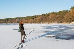 穿过结冰的河的一根年轻美丽的红色头发的画象在森林附近 免版税库存照片