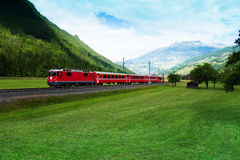 穿过绿色山谷的红色火车在阿尔卑斯附近 免版税图库摄影