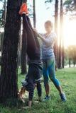 穿运动服的两个女孩训练户外做手倒立反对树在公园 库存照片