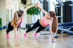 穿运动服的两个女性朋友给上流五,当训练在健身房时的地板上 库存照片
