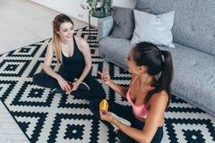 穿运动服的微笑的适合的妇女坐吃果子和谈话的地板 免版税库存图片