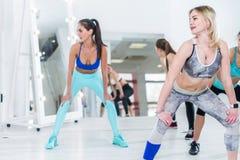 穿运动服的适合的可爱的少妇一起做健身在站立用在膝盖,宽脚的手的健身房 免版税库存图片