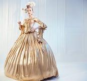 穿金黄维多利亚女王时代的褂子的一名高尚的妇女的画象 免版税库存照片