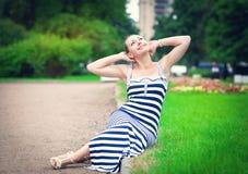 穿镶边的礼服的愉快的美丽的时髦的女人 免版税库存图片
