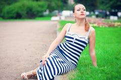 穿镶边的礼服的年轻美丽的时髦的女人 免版税库存图片