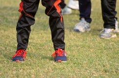 穿长裤&鞋子的玩板球者腿库存照片 免版税图库摄影