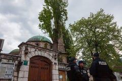 穿防弹夹克的波斯尼亚的警察小分队巡逻在其中一个萨拉热窝的市中心的清真寺前面 免版税库存照片