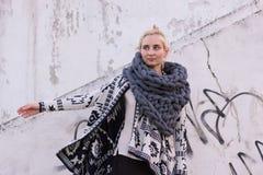 穿阿兹台克黑白夹克和被编织的灰色背心围巾的白肤金发的年轻美丽的时尚女孩 节日成套装备 库存图片