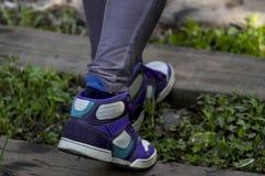 穿鞋子走在铁路路的女孩 免版税库存图片