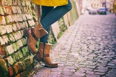 穿黄色外套,牛仔裤和皮鞋的女孩 免版税库存图片