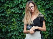 穿黑女衬衫的年轻美丽的长的头发妇女画象,拿着手机在夏天绿色公园反对常春藤背景 免版税库存照片
