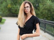 穿黑女衬衫的年轻美丽的长的头发妇女画象,拿着手机在夏天绿色公园道路背景 库存照片