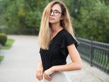 穿黑女衬衫的年轻美丽的长的头发妇女画象,拿着手机在夏天绿色公园道路背景 免版税图库摄影