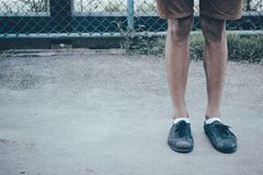穿黑帆布鞋和棕色裤子的一个人腿站立在与拷贝空间的具体地面 免版税库存图片