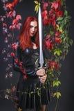 穿黑皮革服装的高美丽的红色顶头女孩拿着幻想剑围拢与秋天颜色留下叶子 免版税图库摄影