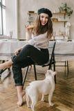 穿黑贝雷帽的一名愉快的妇女的画象拿着新月形面包和法国小狗牛头犬 免版税库存照片
