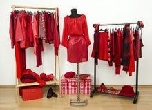 穿戴与红色衣裳的壁橱在挂衣架和成套装备安排了在时装模特。 免版税库存照片