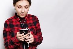 穿戴了听到audiobook或收音机的可爱的年轻行家女孩室内射击在偶然被检查的衬衣在手机有ea的 免版税库存照片