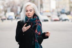 穿戴了步行沿着向下街道和看手机的美丽的金发碧眼的女人在温暖的衣裳 室外纵向 免版税库存照片