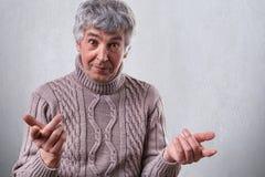 穿戴了站立在白色背景使表示惊奇的成熟人照片在毛线衣握他的手在前面 库存照片