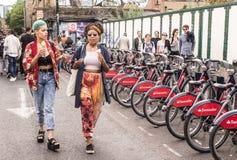 穿戴了走在砖车道的两个行家女孩在凉快的伦敦人样式 免版税库存图片