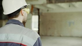 穿戴了走在建筑工地和检查的后面观点的审查员在制服、防护安全帽和镜片 股票视频