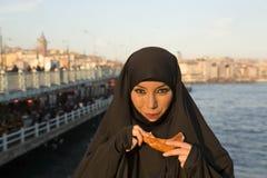 穿戴了黑头巾, chador吃simit,伊斯坦布尔,火鸡的妇女 图库摄影