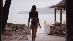 穿黑典雅的泳装的后面观点的性感的白肤金发的妇女站立在大阳台窗口里被放弃的修造在海 股票视频