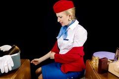 穿戴减速火箭的空中小姐脱下衣服或 免版税库存图片