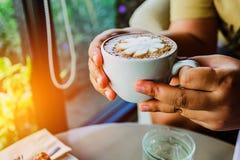 穿戴女孩褂子早晨白色的咖啡杯 妇女拿着一个加奶咖啡杯子 库存图片