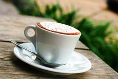 穿戴女孩褂子早晨白色的咖啡杯 库存图片
