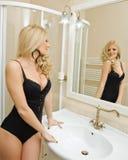 穿黑女用贴身内衣裤的性感的美丽的少妇在卫生间里 在镜子前面的肉欲的金发碧眼的女人在典雅的卫生间里 免版税库存图片
