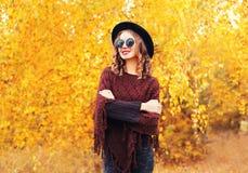 穿黑帽会议太阳镜和被编织的雨披在晴朗的黄色叶子的秋天时尚画象微笑的妇女 免版税库存图片