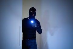 穿巴拉克拉法帽的夜贼拿着手电 免版税库存照片