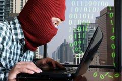 穿巴拉克拉法帽的被掩没的黑客乱砍从膝上型计算机的数据反对数字式城市背景 库存图片