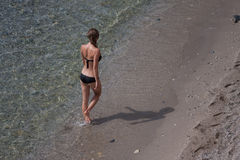 穿黑比基尼泳装的适合的年轻女性走由海滩 库存图片